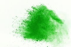 Colored powder explosion. Colore dust splatted. Freeze motion of Green powder exploding on white background royalty free stock photography