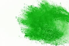 Colored powder explosion. Colore dust splatted. Freeze motion of Green powder exploding on white background royalty free stock image