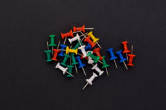 Colored push pins on a black background Royalty Free Stock Images