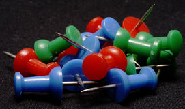 Colored pushpins. A pile of red, green, and blue pushpins on a black background Royalty Free Stock Images