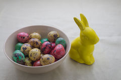 Colored quail eggs in a bowl. Bowl with colored quail eggs and ceramic rabbit on textile backg Stock Photos