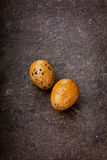 Colored quail eggs by Easter. On a brown surface Royalty Free Stock Photography