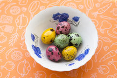 Colored quail eggs on a plate stock images