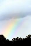 Colored rainbow through dark sky Stock Images