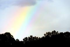 Colored rainbow through dark sky Stock Photos