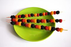 Colored raspberries on wooden sticks on a green plate stock photos