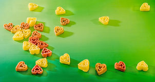 Colored (red, yellow an orange) heart shape pasta, colored degradee bokeh background, close up Stock Photo