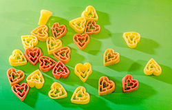 Colored (red, yellow an orange) heart shape pasta, colored degradee bokeh background, close up Royalty Free Stock Image