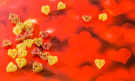 Colored (red, yellow an orange) heart shape pasta, colored degradee bokeh background, close up Stock Photography