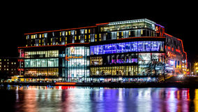 Colored reflections from a large office building on water. Night view of a large private office building. Multi colored curvy reflections on a lake. Big building Royalty Free Stock Photo