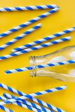 Colored, reusable, paper, striped, blue and white straws for drinking juice or cocktail life, in a glass bottle, on a yellow royalty free stock images