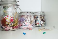 Colored ribbons and colorful buttons in glass jars for creating artistic hobbies stock photo
