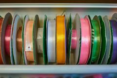 Colored ribbons for needlework on coils in the store.  royalty free stock image
