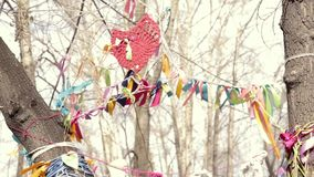 Colored ribbons on a wish tree, sacred place and symbolic tradition. Bands are swaying in the wind stock footage