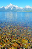 Colored rocks lay beneath clear cold waters. Stock Photo