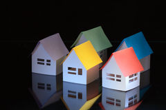 Colored roofs. Few toy papery houses with colored roofs on dark background Stock Images