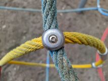 colored rope cables fastened together with a metal fastener