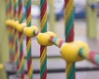 Colored ropes in the playground. Multicolored ropes with plastic fastenings on the playground in the park royalty free stock image