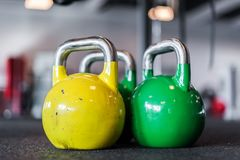 Colored round dumbbells in sport center stock images