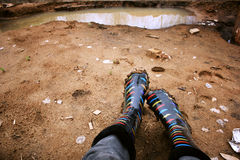 Colored rubber boots in the mud. Legs in colored rubber boots soiled with clay, amid puddles Royalty Free Stock Photography