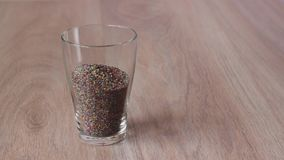 Colored sand is poured into the glass and seashells placed on top stock footage
