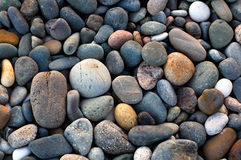Colored sea pebbles background. A close-up of coarse dry multicolored sea pebbles royalty free stock photo