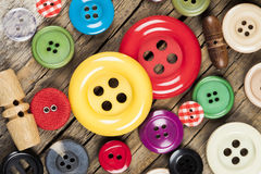 Colored sewing buttons on wooden background Royalty Free Stock Photography