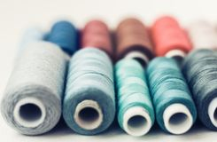 Colored sewing thread coils on white background with copy space for text royalty free stock photo