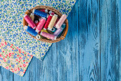 Colored sewing threads on a old work table Stock Photos