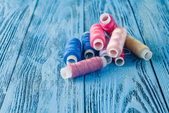 Colored sewing threads on a old work table Royalty Free Stock Photography