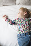 Colored shirt baby sleeping on white bed. Blonde caucasian baby face nineteen month age with colored shirt sleeping on white sheets king bed stock image