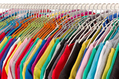Colored shirts on hangers steel closeup. Royalty Free Stock Photos