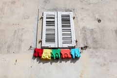 Colored shirts hanging to dry under the window pan Stock Photo