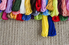 Colored skeins of thread lie on a natural linen background top, Stock Photography