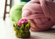 Colored skeins of wool in the foreground flowers.  Royalty Free Stock Photography