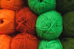 Colored skeins of wool on a store shelf. Woolen skeins for knitting all the colors of the rainbow, green, brown, red and orange