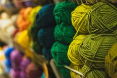 Colored skeins of wool on a store shelf. Woolen skeins for knitting all the colors of the rainbow, blue, green, brown, yellow, red