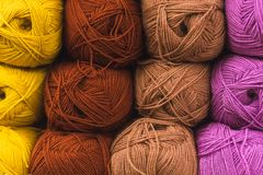 Colored skeins of wool on a store shelf. Woolen skeins for knitting all the colors of the rainbow, brown, yellow, red and purple