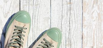 Laced sneakers stand on a white wooden background. Summer, sports shoes top view. stock photos