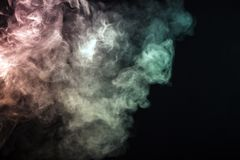 Colored smoke on a black background. The concept of light show a royalty free illustration
