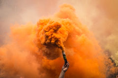 Colored smoke. Hand holds the colored smoke bomb Royalty Free Stock Image