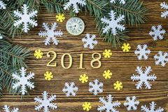 New Year composition with clock, snowflakes and fir branches. Colored snowflakes and spruce branches lie on the wooden background royalty free stock image