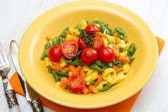 Colored spatzle on yellow dish Stock Photo