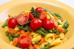 Colored spatzle on yellow dish Stock Image