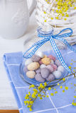 Colored speckled chocolate Easter eggs in crystal bell jar with ribbon on blue napkin on white table, basket with yellow flowers Royalty Free Stock Photos