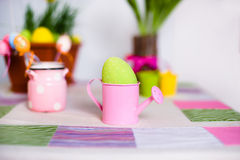 Colored speckled egg in a small pink watering pot Stock Photo