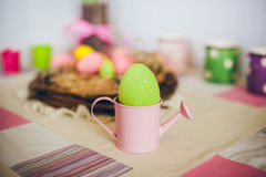 Colored speckled egg in a small pink watering pot Royalty Free Stock Photography