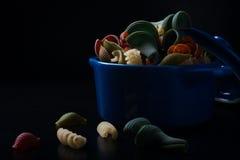 Colored spelt pasta in blue ceramic pot Stock Photography