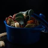 Colored spelt pasta in blue ceramic pot Stock Images