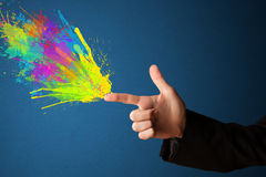 Colorful splashes are coming out of gun shaped hands. Colored splashes are coming out of gun shaped hands stock image